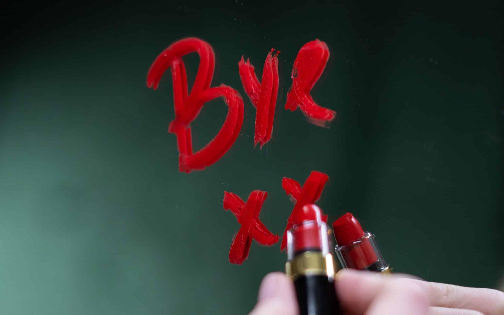 """Uma mão escrevendo """"bye"""" com um batom vermelho num espelho."""