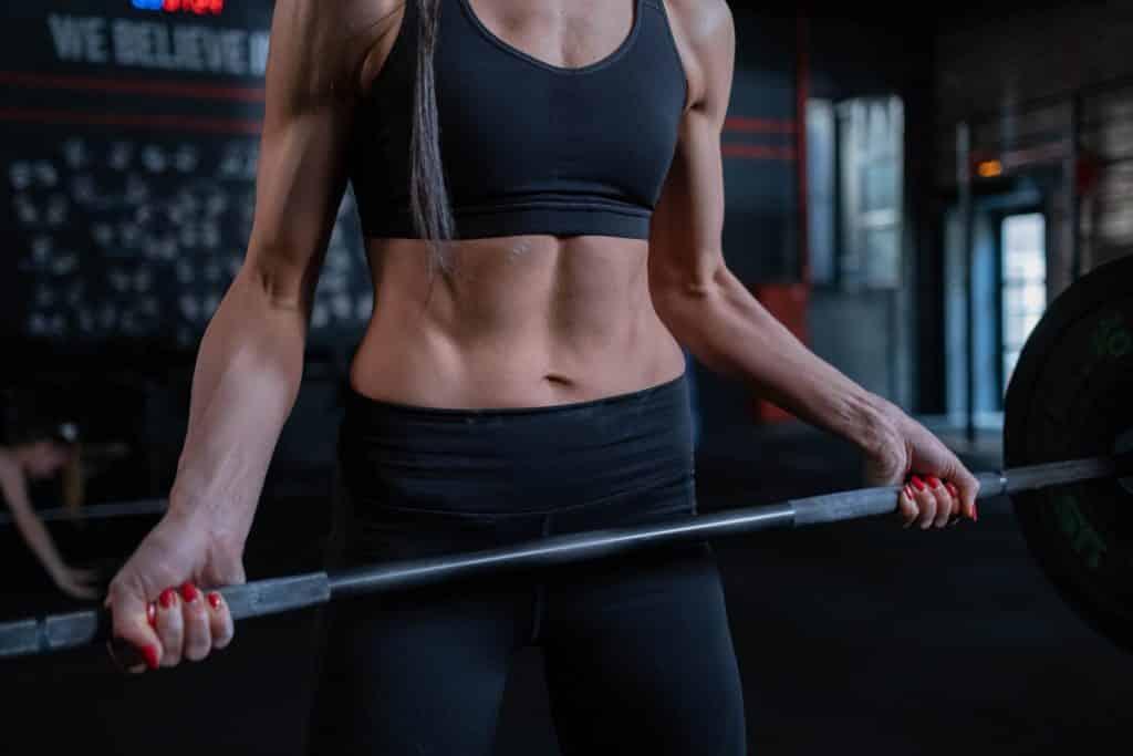 Uma mulher de leggings levantando uma barra com pesos.