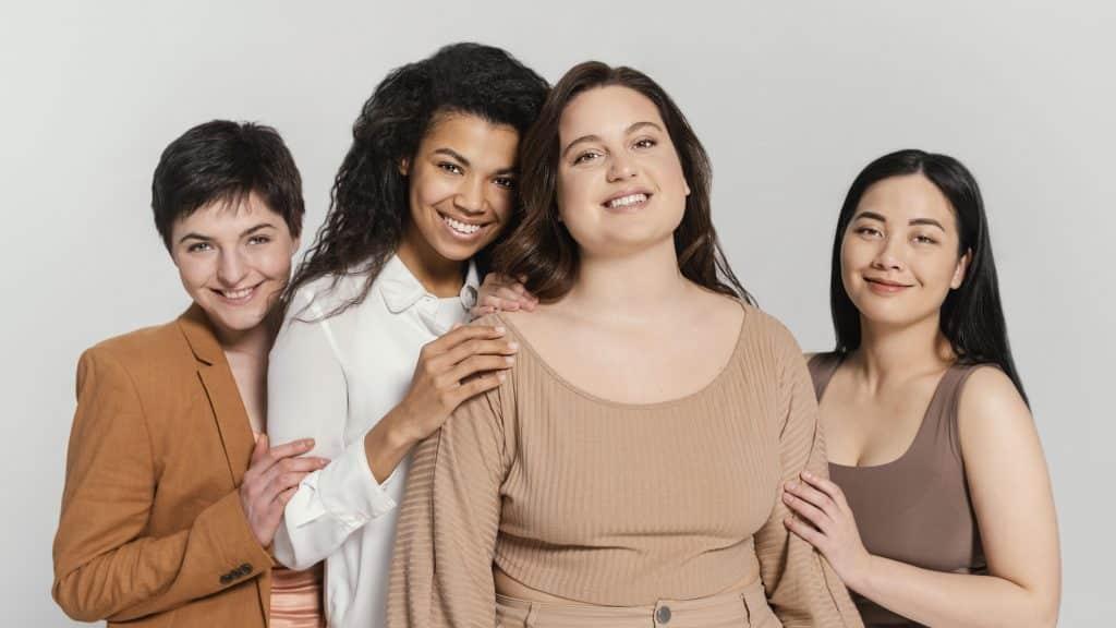 Quatro mulheres etnicamente e fisicamente diferentes, uma do lado da outra, representando a diversidade feminina