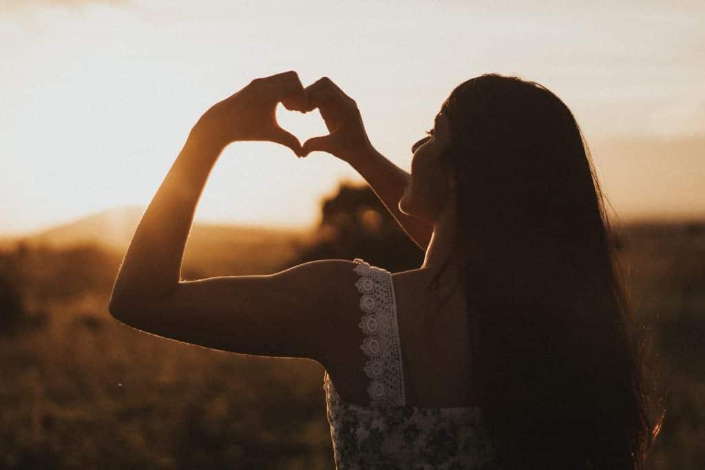 Mulher branca de costas com as mãos formando coração.