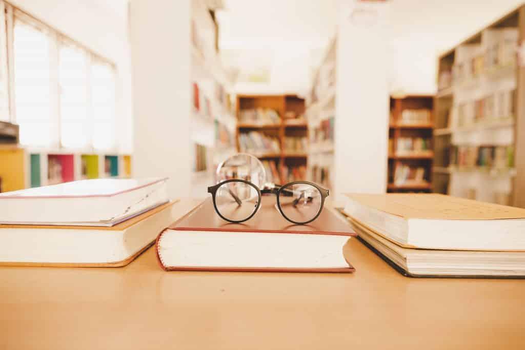 Livro com um óculos em cima colocado sobre uma mesa com outros livros rodeando-o. Ao fundo, desfocado, prateleiras com outros livros.
