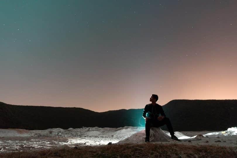 Homem sentado numa pedra observando o céu.