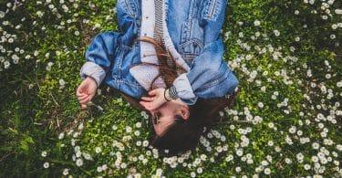 Mulher branca deitada numa grama com flores brancas.