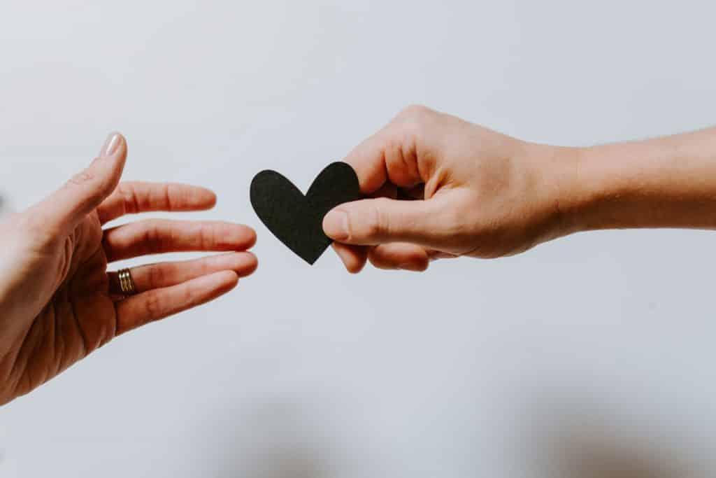 Mão branca segurando coração preto.
