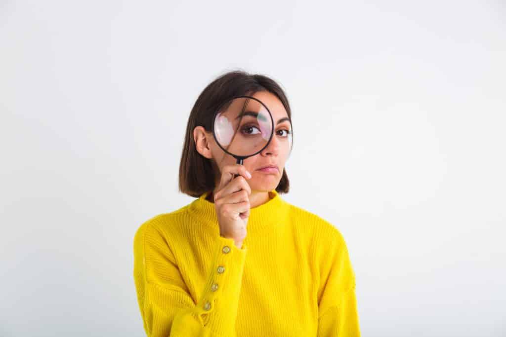 Uma mulher morena com um suéter amarelo olhando através de uma lupa.
