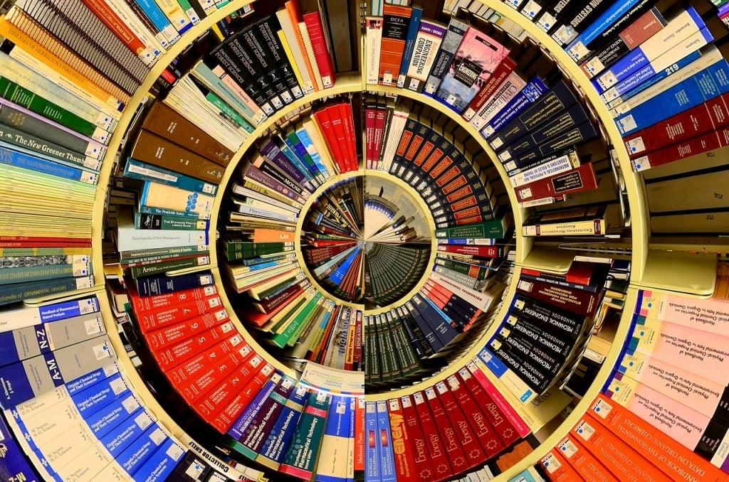 Vários livros reunidos em prateleiras. Imagem distorcida de maneira circular.