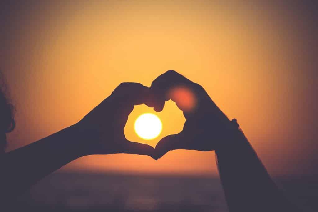 Mãos em formato de coração ao redor do Sol.