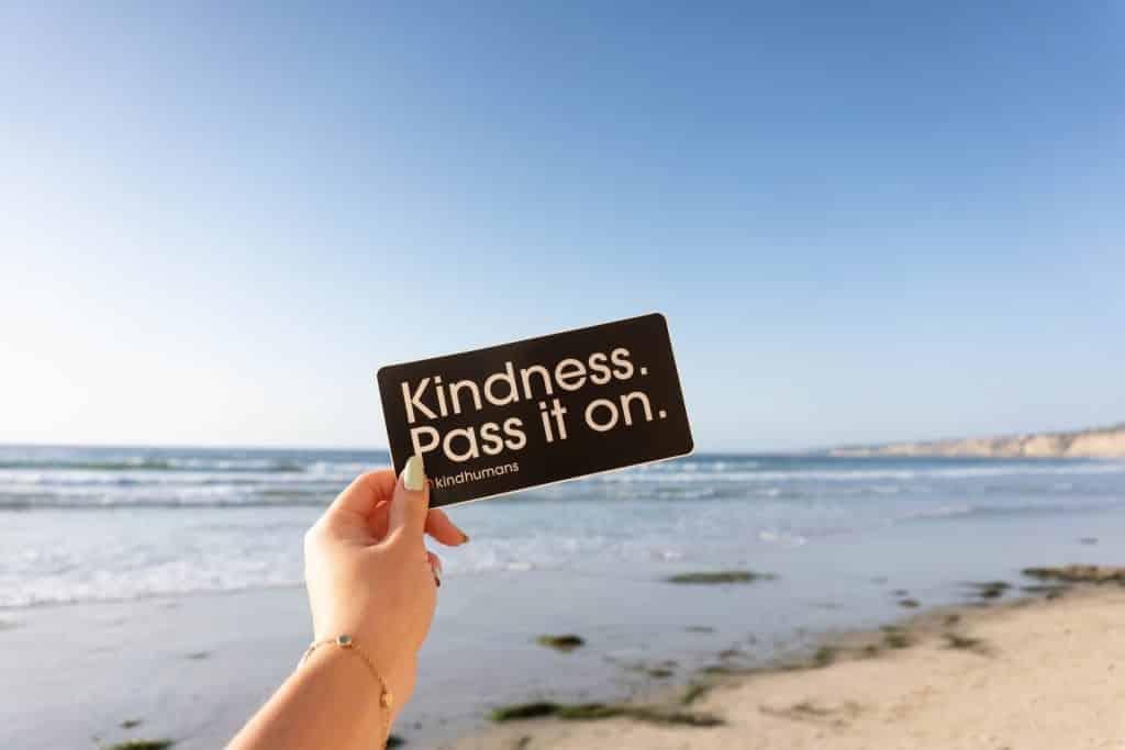 """Mão branca segurando papel escrito """"Kindness. Pass it on."""""""