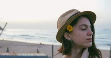 Mulher branca com flor no cabelo e olhos fechados.