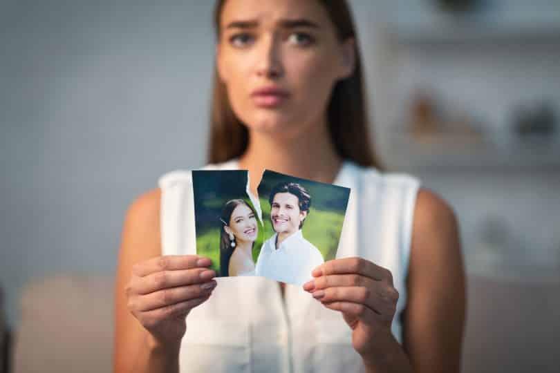Uma mulher rasgando uma fotografia que tem um homem e uma mulher.