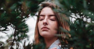 Mulher branca de olhos fechados no meio de folhas.