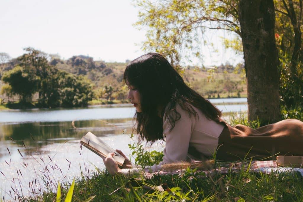 Mulher asiática deitada na grama lendo livro.