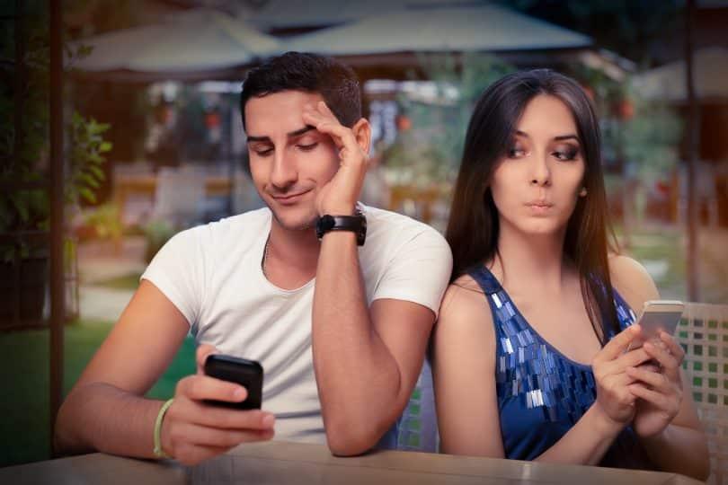 Um homem mexendo num celular e à esquerda uma mulher bisbilhotando o celular dele.