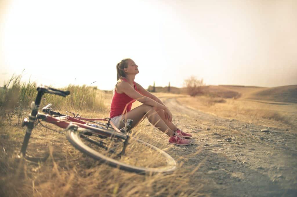 Mulher branca sentada numa estrada ao lado da bicicleta.