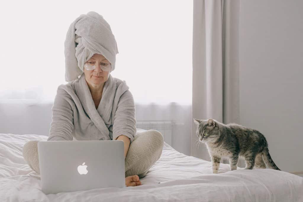 Uma senhora de roupão mexendo no laptop com seu fato ao lado