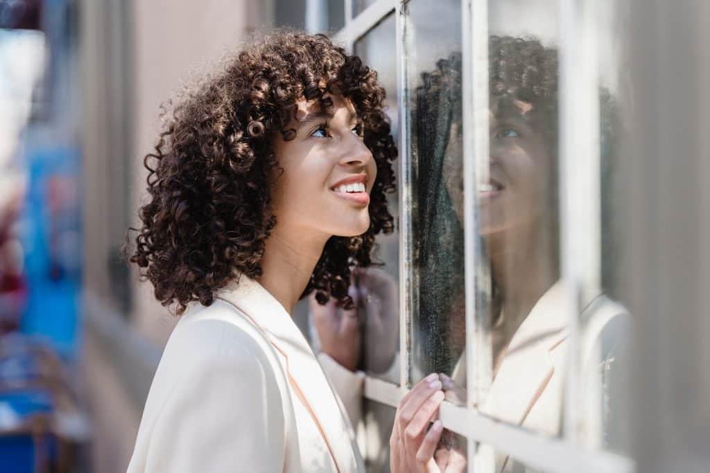 Mulher sorrindo olhando para uma janela