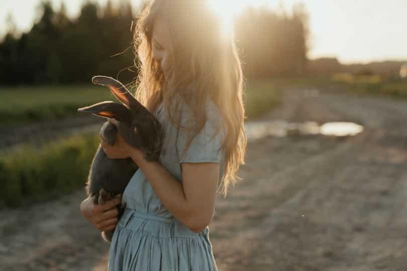 Criança segurando um coelho preto