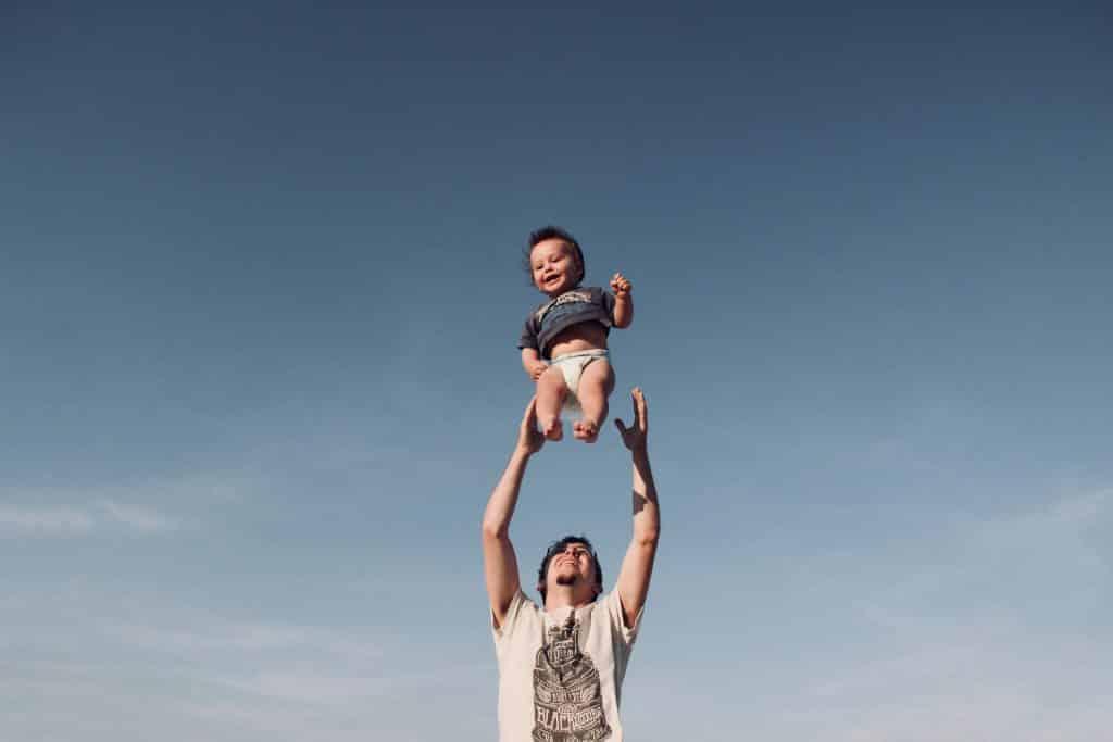 Pai jogando o seu bebê para o alto