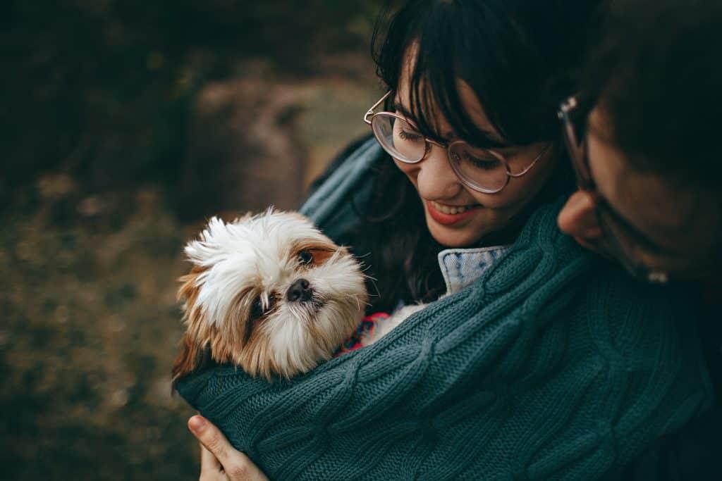 Casal abraçando um cachorrinho