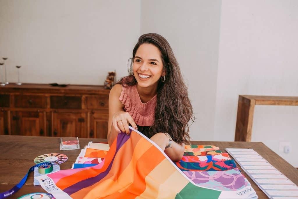 Mulher sorrindo enquanto segura uma bandeira colorida