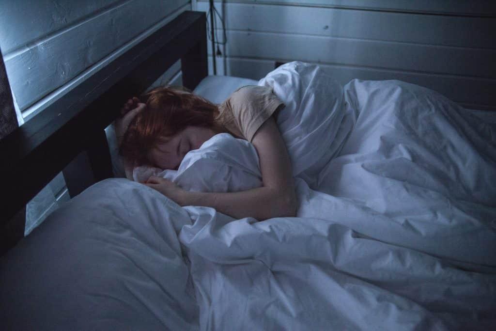 Mulher dormindo em sua cama durante a noite