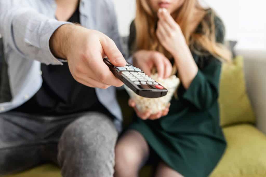 Homem segurando um controle para dar play em um filme