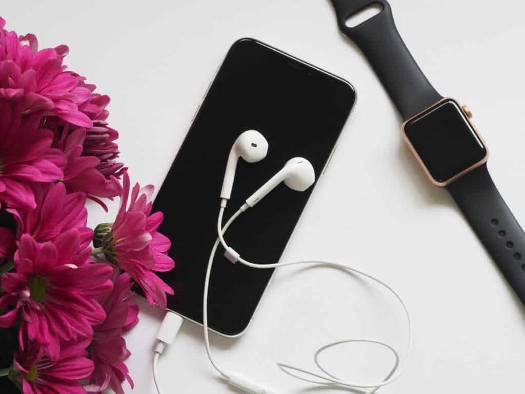 Celular, fone de ouvido e relógio eletrônico