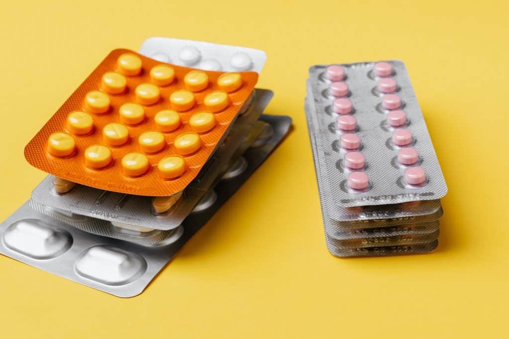 Várias cartelas de comprimidos sobre uma superfície amarela