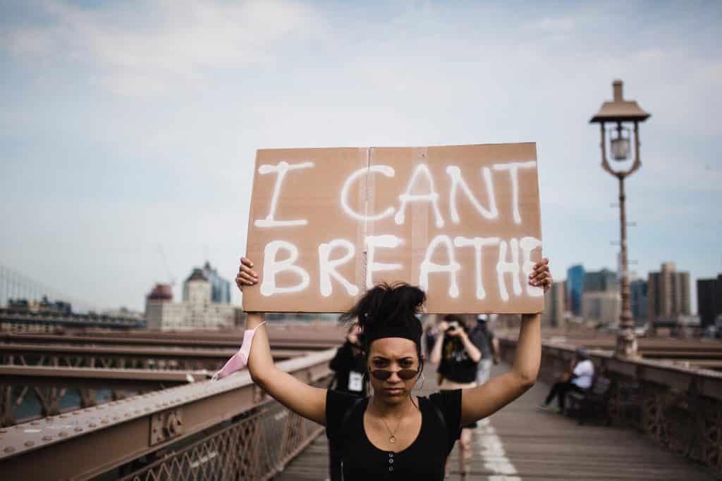 Uma mulher negra segurando uma placa escrito i cant breathe