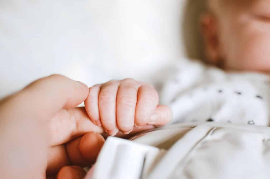 Bebê branco segurando dedo de adulto branco.