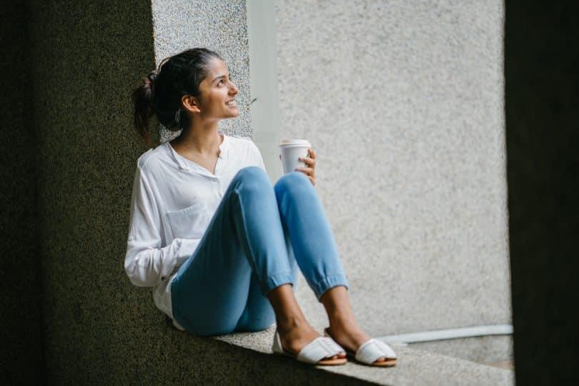 Mulher marrom sentada num muro segurando copo.