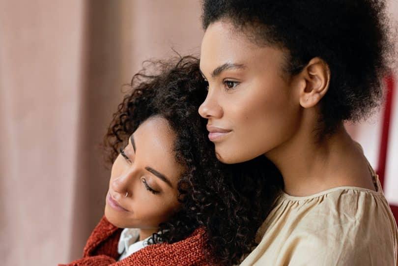 Mulheres negras com as cabeças encostadas.