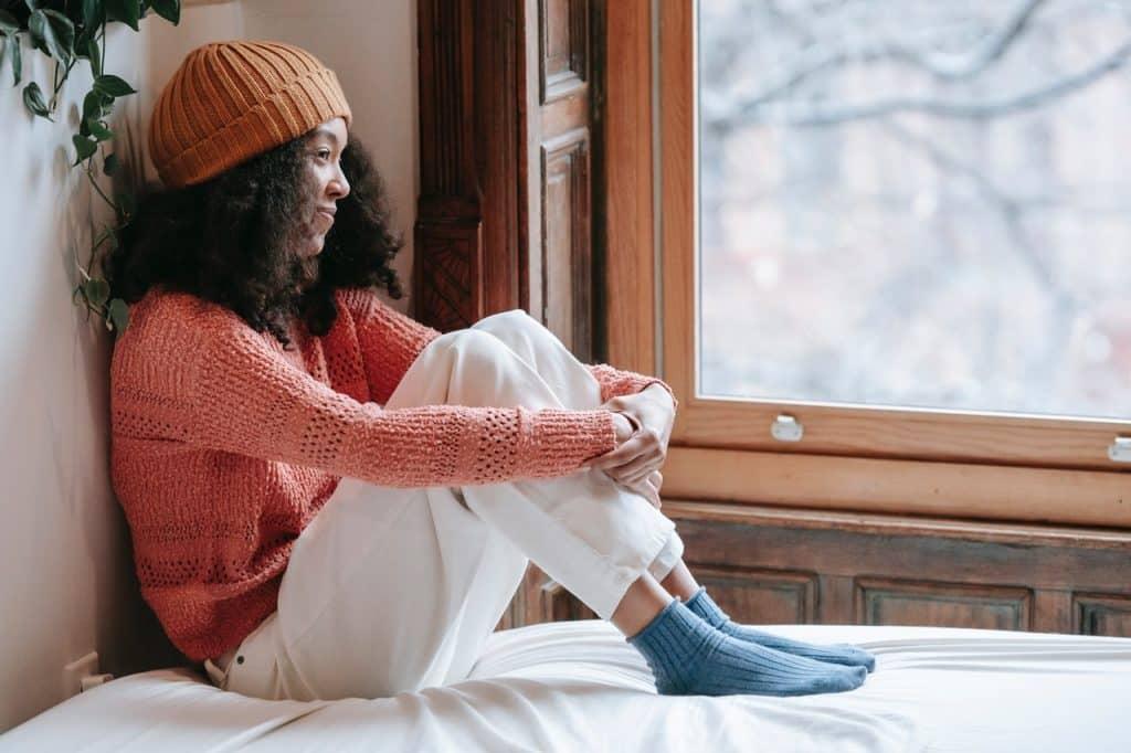 Menina sentada na janela com as mãos segurando os joelhos.