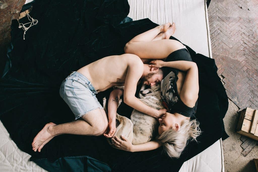 Um casal dormindo com um cachorro
