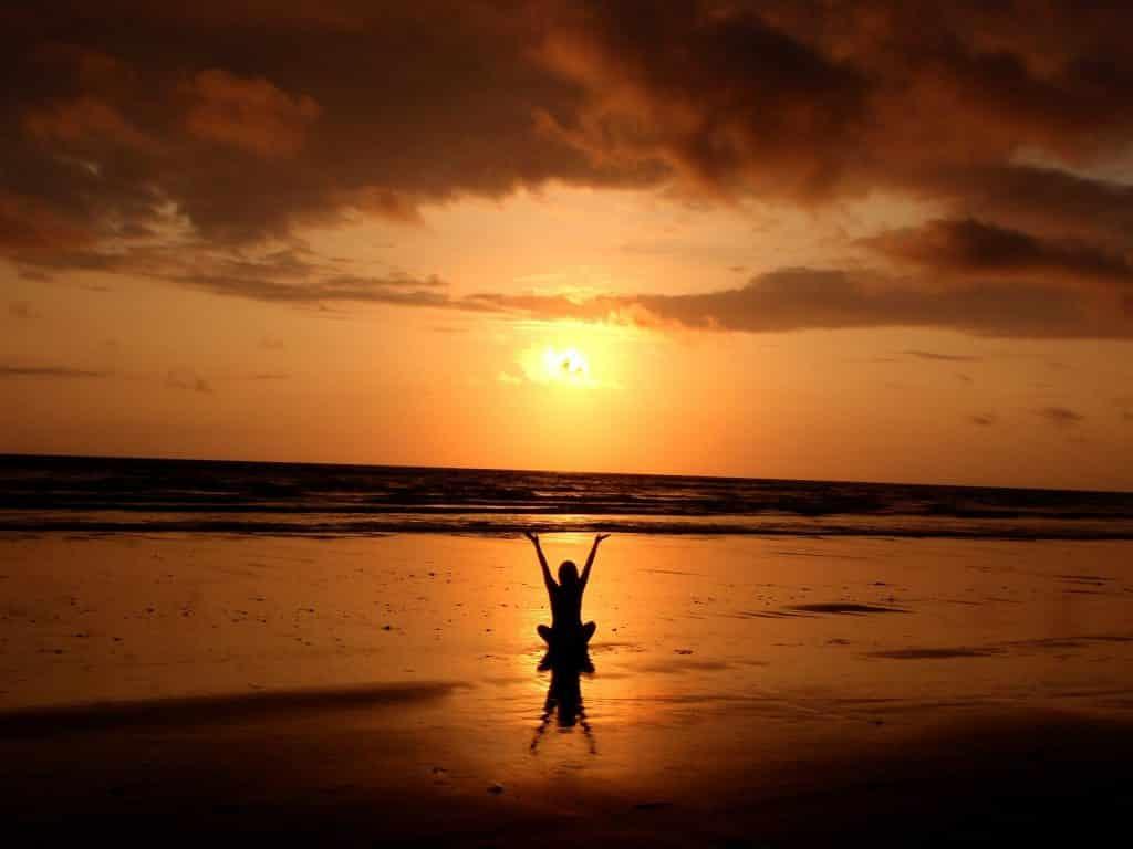 Mulher assistindo ao pôr do sol na praia