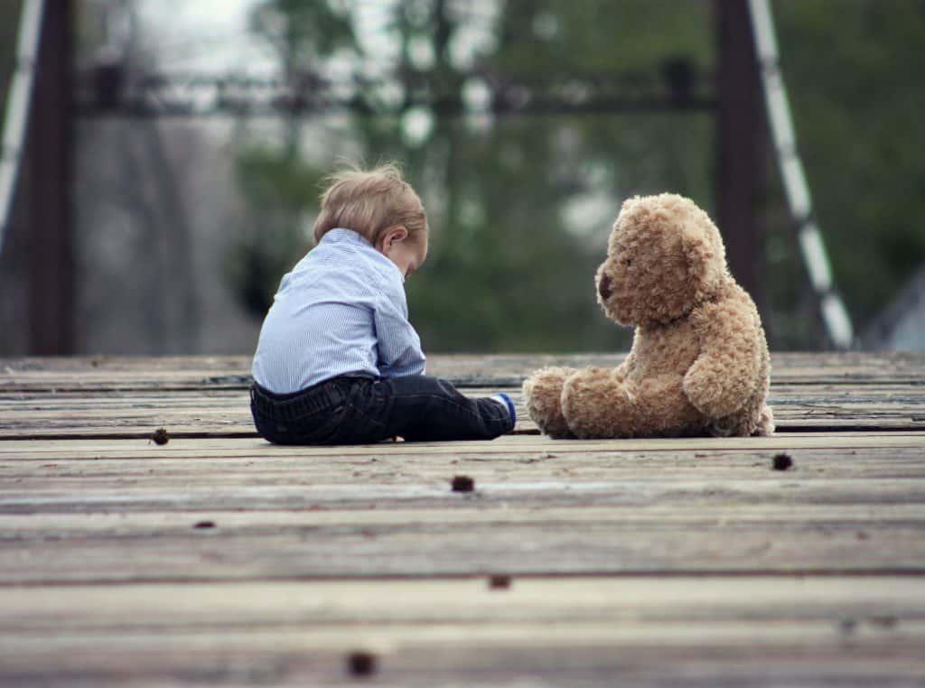 Bebê ao lado de um urso de pelúcia