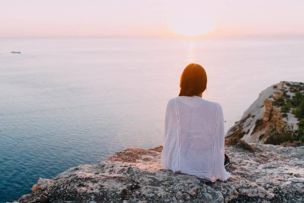 Mulher sentada em uma rocha em frente ao pôr do sol