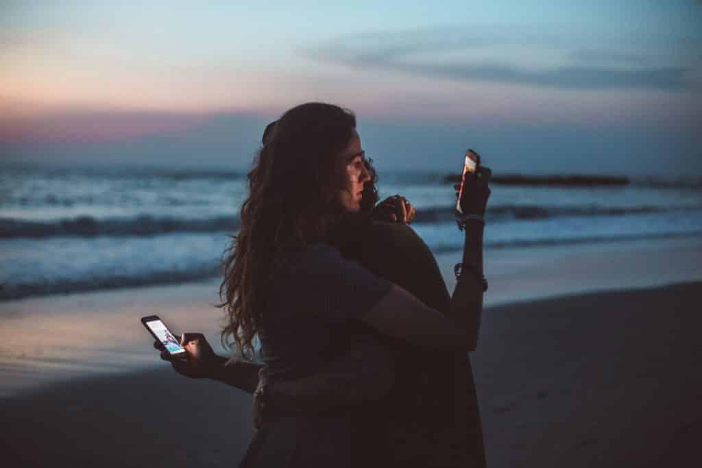 Uma mulher e um homem abraçados olhando, cada um, o seu celular