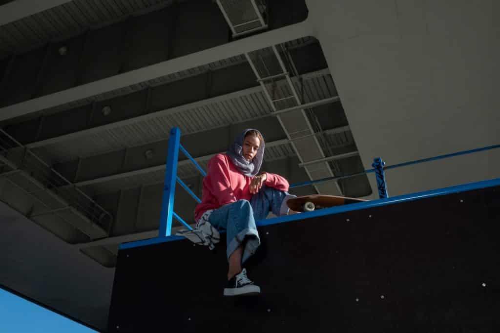 Mulher sentada em uma pista de skate.