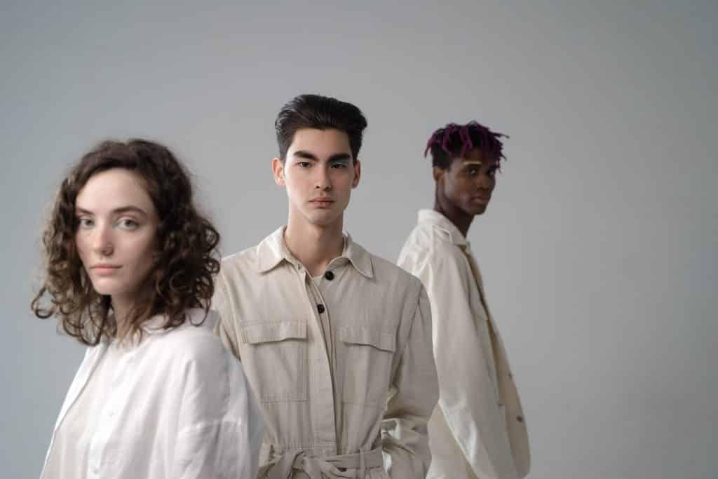 Três pessoas diferentes de camisa branca uma atrás da outra em um estúdio branco