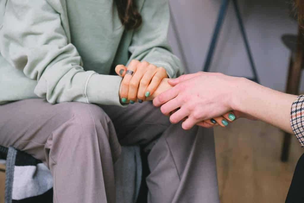 Uma mulher ajudando outra mulher enquanto segura suas mãos
