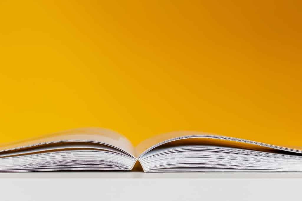 Um livro aberto em frente de um plano de fundo amarelo