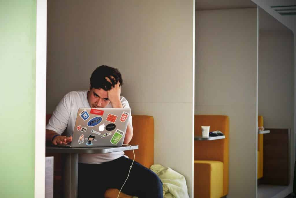 Homem estressado de frente para seu computador