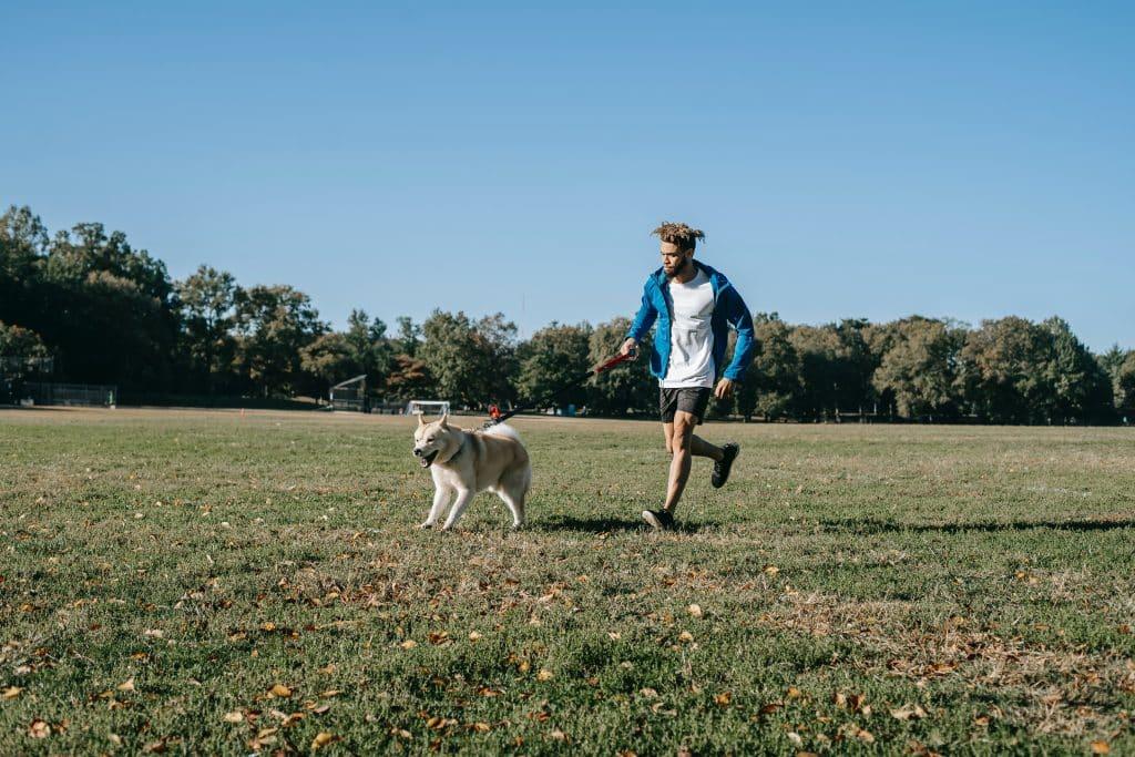 Homem correndo com seu cachorro em um campo