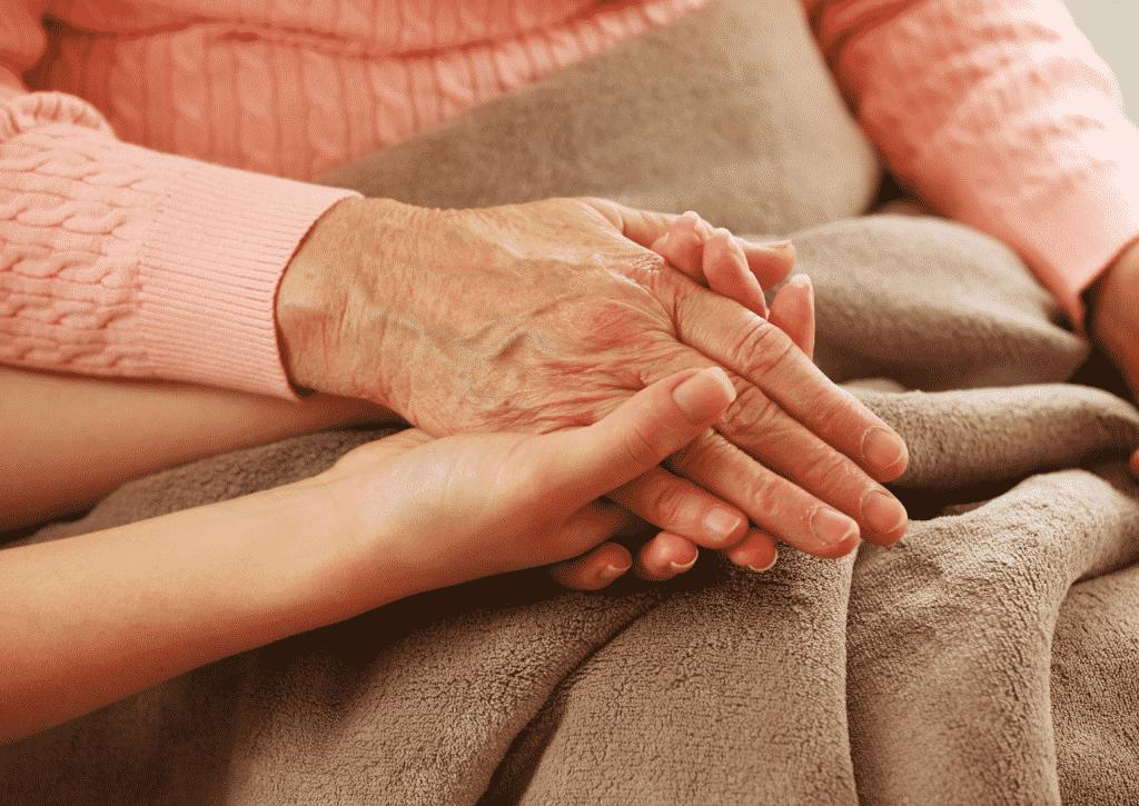 Uma mão feminina segurando uma mão feminina idosa.