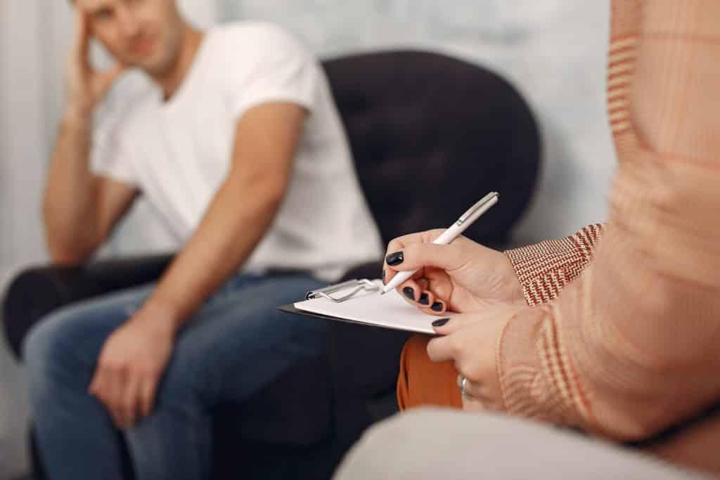 Uma mulher fazendo anotações em um bloco. Ao fundo, um homem sentado em uma poltrona, apoiando sua cabeça sobre sua mão esquerda.