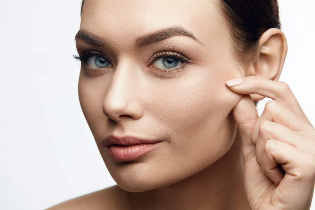 Uma mulher branca esticando uma parte da sua pele do rosto.