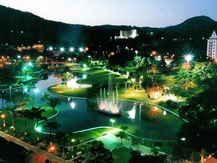 Uma área repleta de luzes, com um lago circular  no meio. No seu entorno, zonas verdes com árvores, instalações e construções. Ao fundo, montes verdes.