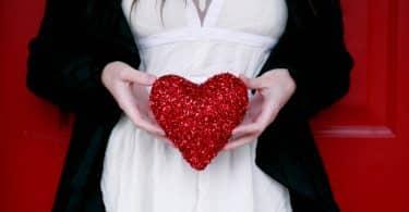 Mulher branca segurando coração vermelho.