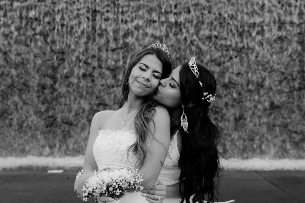 Mulheres brancas com vestidos de noiva abraçadas.